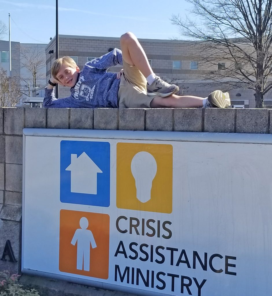 Middle schooler Webb poses at Crisis Assistance Ministry Sign