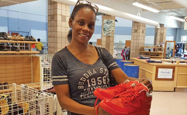 Smiling woman in store holding tennis shoes