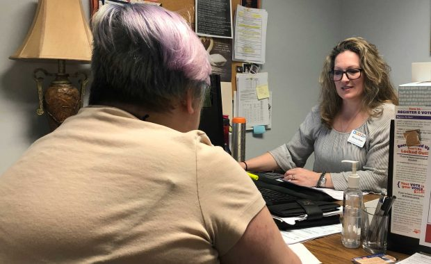 A woman seeking financial assistance sits across the desk from a caseworker during an interview for assistance.