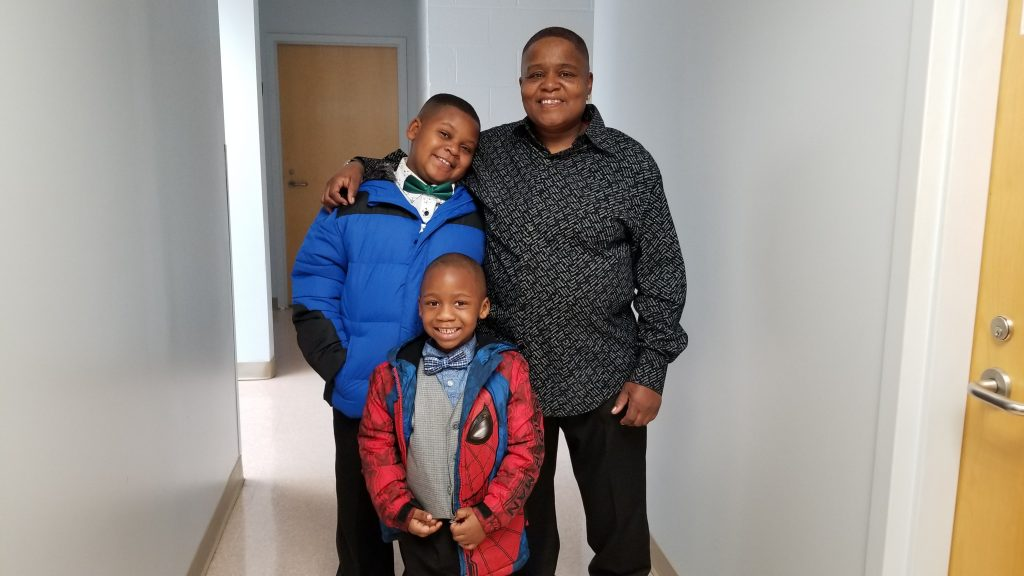 Betty poses with her grandsons who are wearing warm coats they selected free-of-charge from Crisis Assistance Ministry's Free Store.