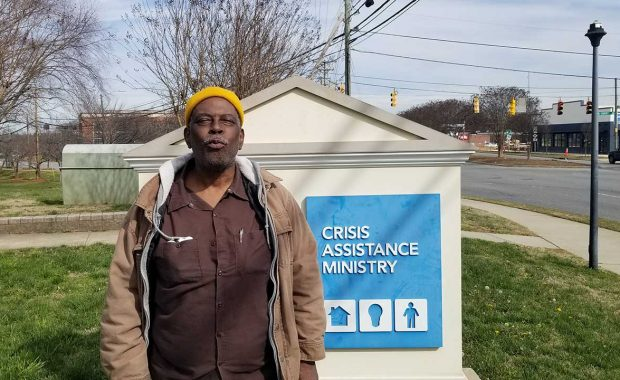 Myron stands in front of Crisis Assistance Ministry sign