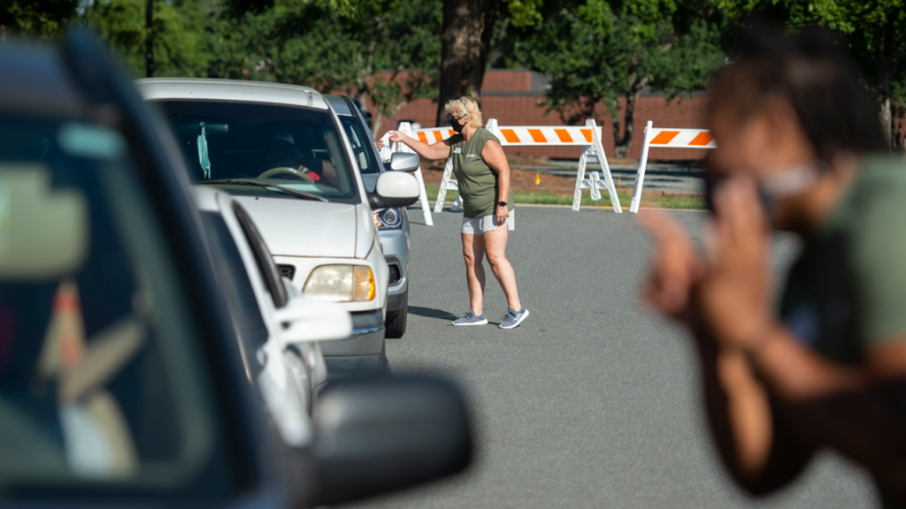 Volunteers wearing face coverings interact with individuals in cars lined up for services.