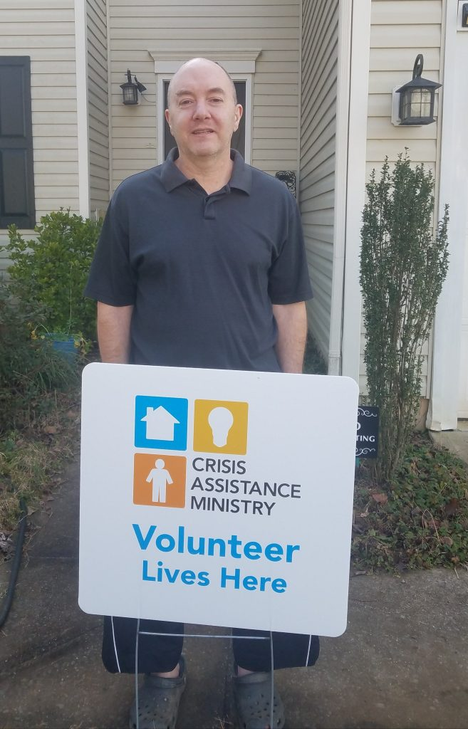 Kurt poses outside his home with a Crisis Assistance Ministry Volunteer Lives Here sign.