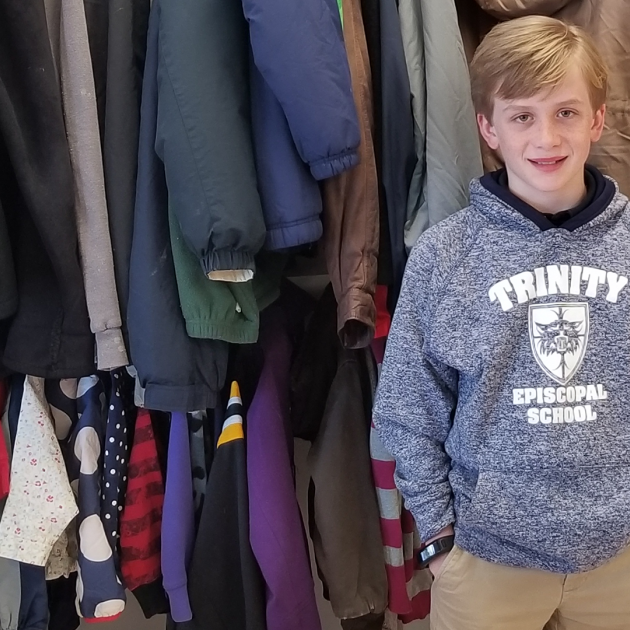 Happy 11 yo poses in Free Store wearing Trinity Episcopal School sweatshirt.