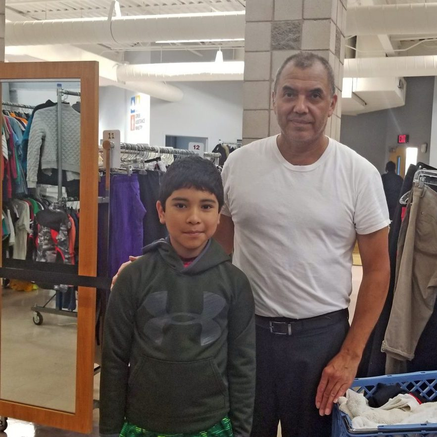 Father and son stop to show off a green hoodie that's just right during their shopping trip in the Free Store.