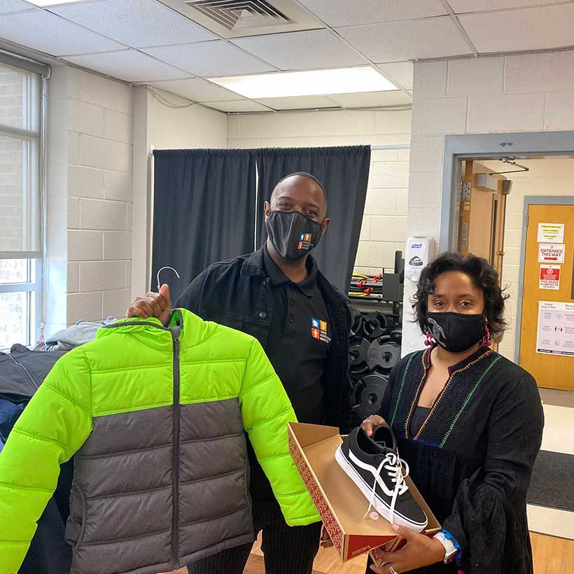 Phillip Miller holds a bright new coat with Raukell Robinson holding new shoes for CMS students.