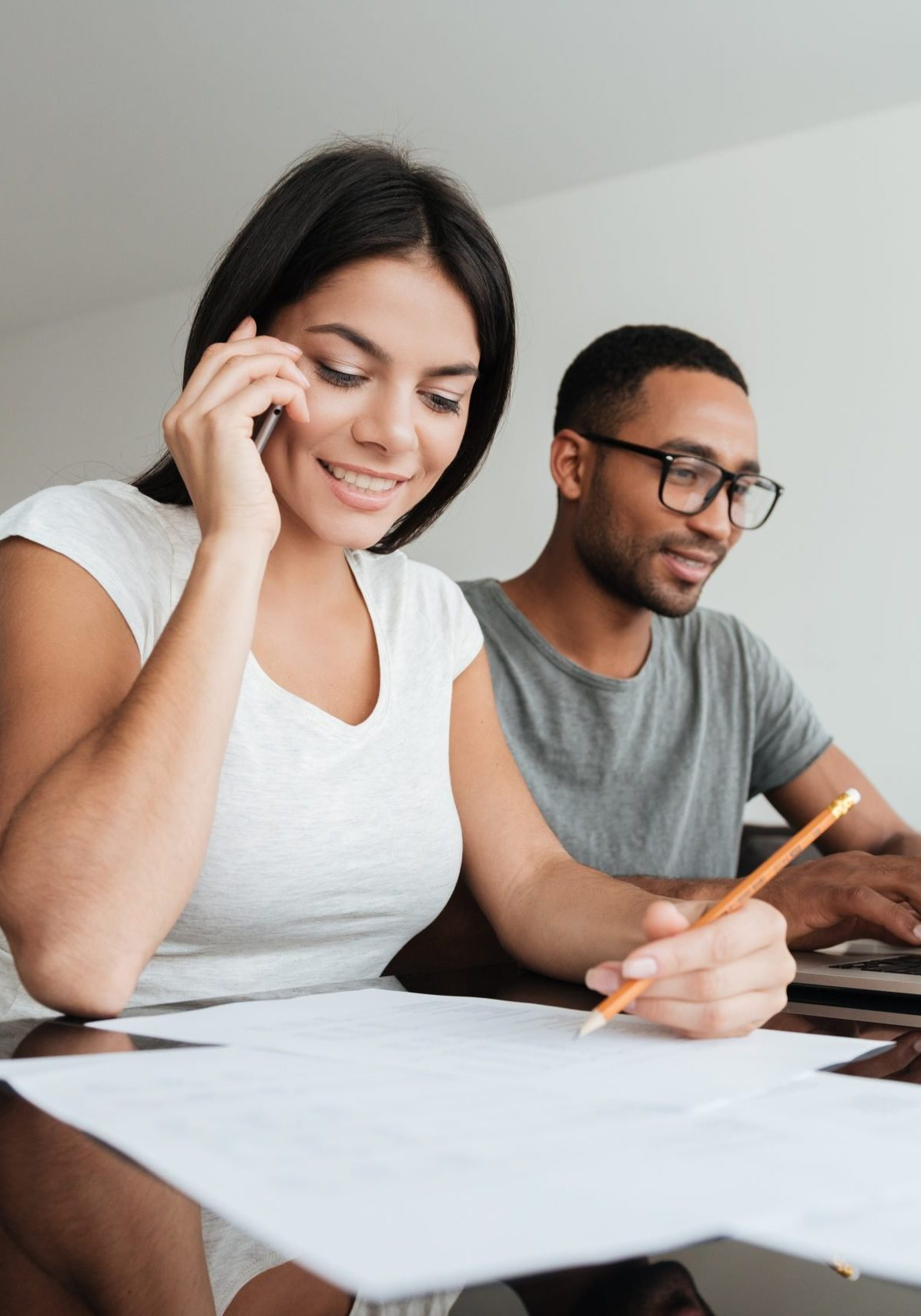 Photo of happy loving young couple analyzing their finances with documents. Man look at laptop. Woman talking by phone.